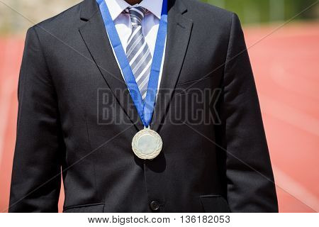 Mid section of businessman wearing gold medal and standing on running track