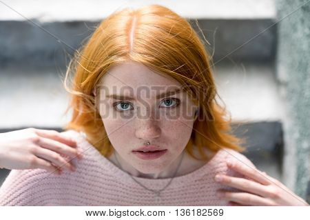 Red-haired Girl Standing On The Stairs And Looking At The Camera. Redhead. Jeans.