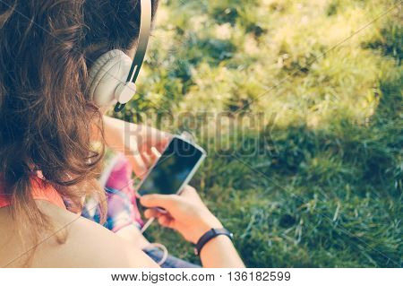 Cropped image of a girl in headphones listen to music and use a smart phone on the lawn in the summer yellow toning