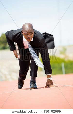Businessman with laptop ready to run on running track