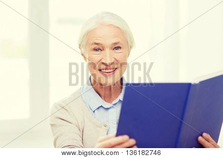 age, leisure and people concept - happy smiling senior woman reading book at home