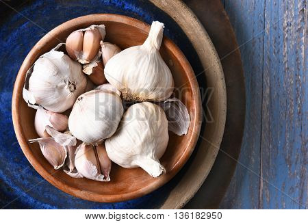 HIgh angle view of a bowl of garlic bulbs and cloves in a blow, on a rustic blue table.