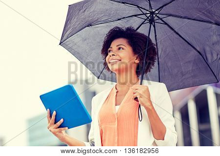 business, bad weather and people and concept - happy african american businesswoman with umbrella and tablet pc computer at city street