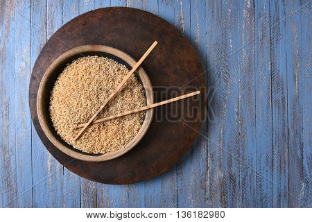 Brown Rice and Chop Sticks on a rustic blue wood table. Top view with copy space.