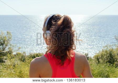 Girl with headphones and a red tank top looking at the sea in the summer, the view from the back