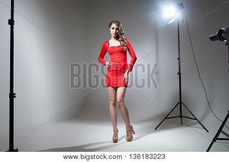 Seductive young model in red dress in spotlight.Studio shot