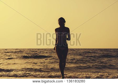 Woman In A Swimsuit Runs Out Of The Water On The Beach