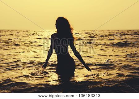Silhouette Of A Slender Woman In The Water At The Beach In Sunshine