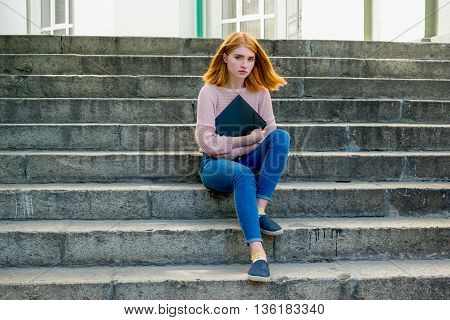 Red-haired Girl Sitting On The Stairs