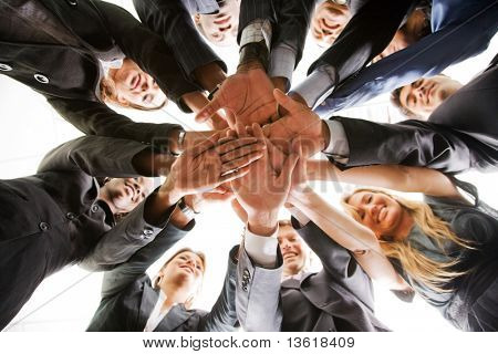 business people teamwork in an office with hands together - isolated