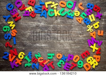 Top border of colorful magnetic letters and numbers over a wooden background