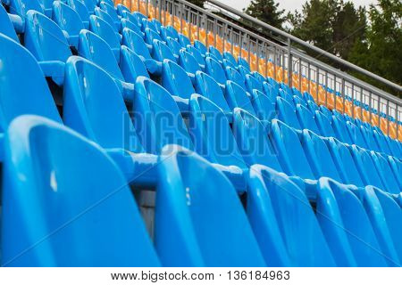 Rows of empty blue and orange chairs on a soccer stadium