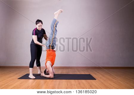 Yoga Instructor Guiding Student Perform Head Stand Pose Or Sirsasana