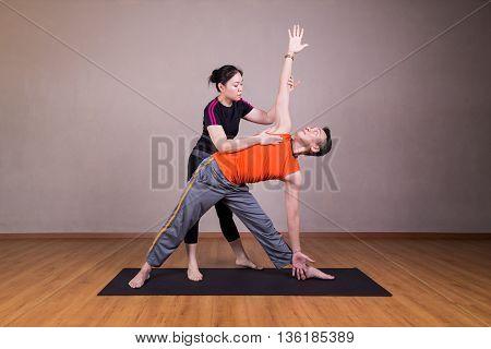 Yoga Instructor Guiding Student Perform Triangle Pose Or Trikonasana