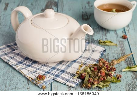 Teapot on a napkin, sprigs of the dried of wild strawberry and a cup of tea on a blue wooden background.