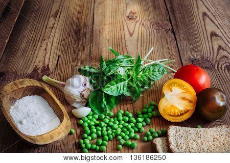 Basil, color tomatoes, garlic, green peas, salt and crispbread in wood background