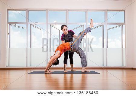 Yoga Instructor Assisting Student Perform Backbend Or Chakrasana Pose