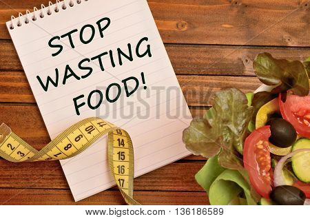 The words Stop wasting food on notebook
