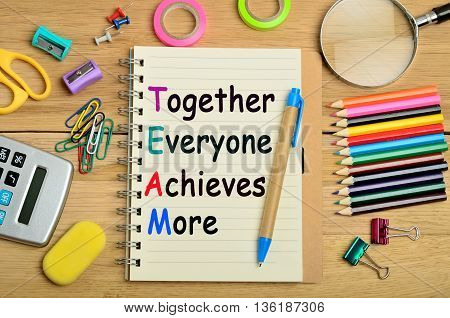 The words Together Everyone Achieves More on notebook