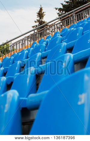 Rows of empty blue chairs on a soccer stadium, the open blue sky