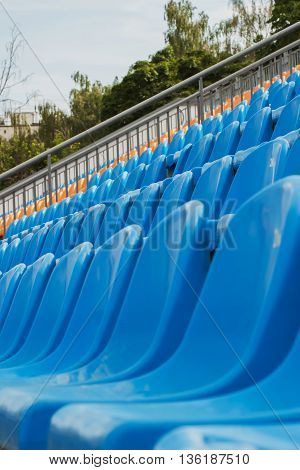 Rows of empty plastic chairs on stadium, the open blue sky