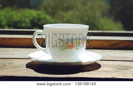 White cup of coffee on old wooden windowsill