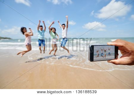 Somebody taking photo of friends jumping at the beach