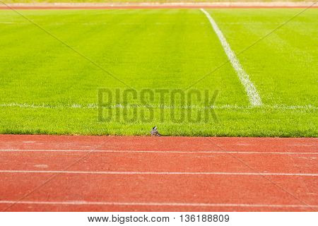 Athletic tracks in stadium for athletes around an football field with natural grass