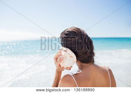 Portrait of smiling woman listening shellfish on the beach