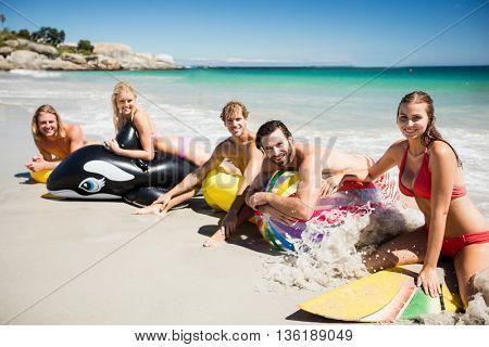 Friends lying on buoy on the beach