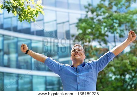 Man with arms raised outdoors
