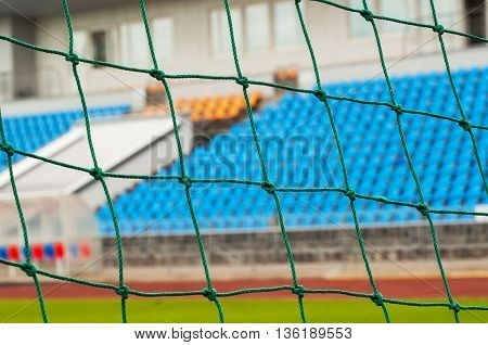 Rows of empty blue chairs on a soccer stadium through the soccer goal net
