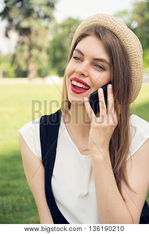 Hipster Girl With Trendy Look Talking On Smartphone In Park