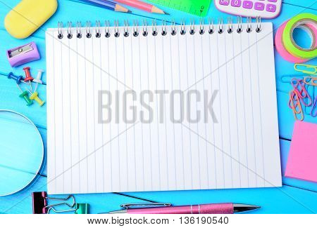 Many objects school on blue wooden table