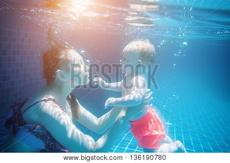Happy mother and her  baby  dive down  in a pool.