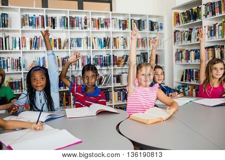 Pupils raising their hands in library