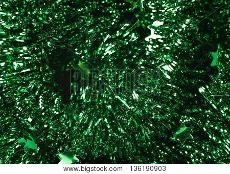 Surface covered with the tinsel green garland as an abstract background texture