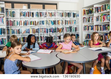 Happy pupils are studying in library