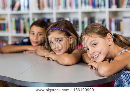 three pupils posing for the camera at desk in library