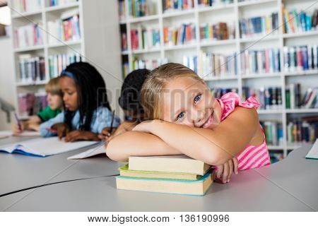 Little girl posing arm crossed at desk in the library