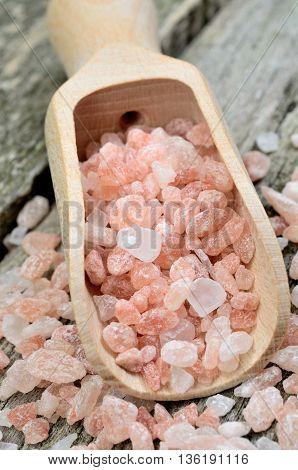 Pink salt himalayan in wooden scoop on rustic table