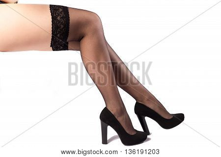 Woman legs in black stockings and high heels isolated on the white background