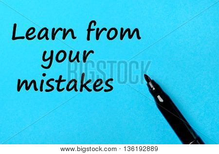 The words Learn from your mistakes on blue paper