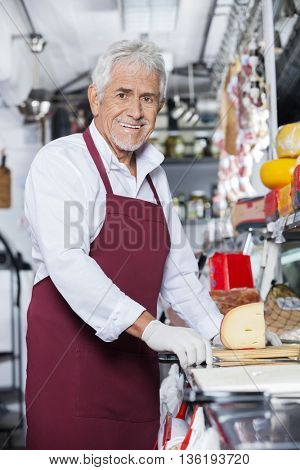 Happy Salesman Standing At Counter In Cheese Shop