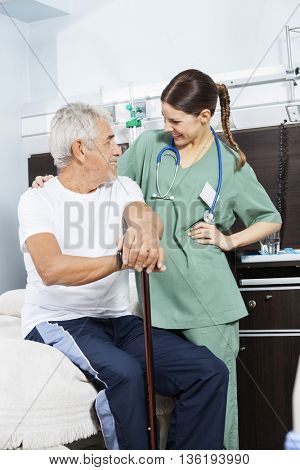 Senior Patient And Young Nurse Looking At Each Other