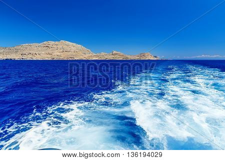 View from the sea on the rocks, and the trace of the boat. Greece Rhodes Island