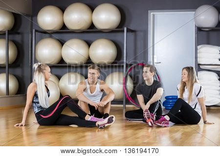 Friends Communicating While Sitting On Floor In Gym