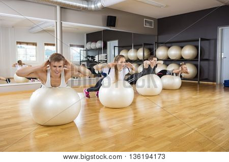 Friends Performing Back Extension Exercise On Balls