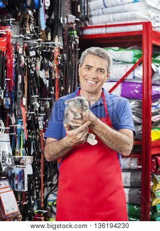 Smiling Salesman Holding Rabbit In Pet Store