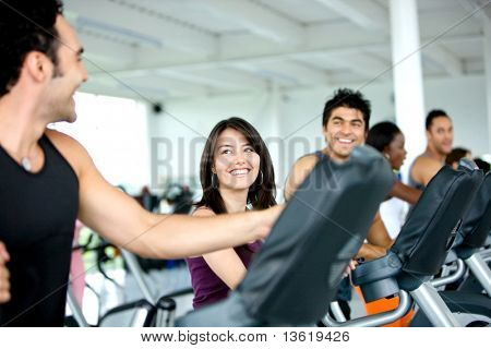 Group of friends laughing while exercising at a gym